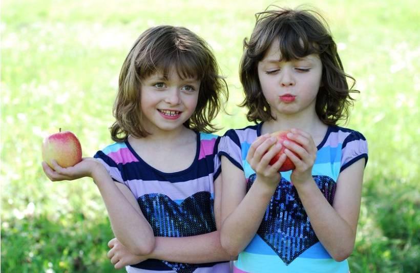 2 girls standing outside, holding apples