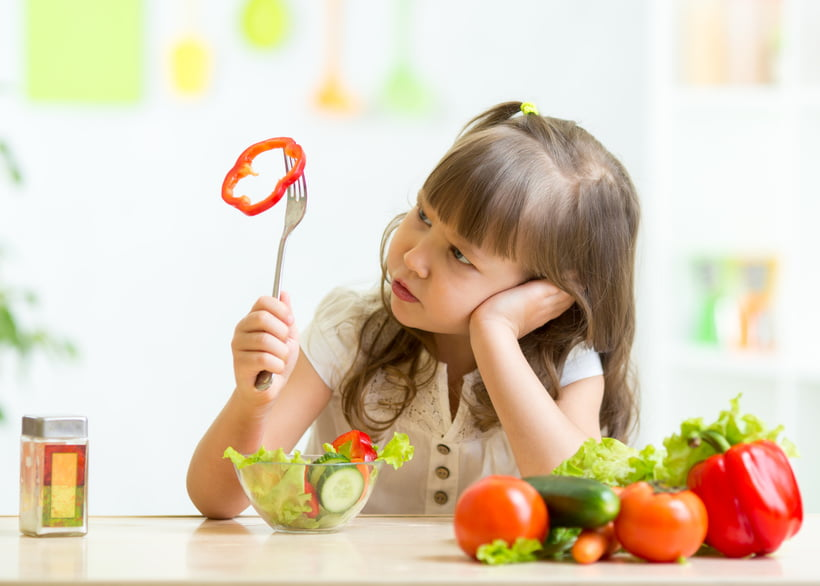 image of little girl sitting at dinner table, frowning at her vegetables