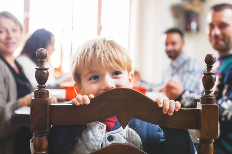image of preschool child peeking over dining room chair at family meal