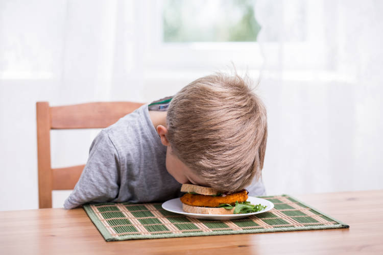 image of unhappy kid faceplanting on the sandwich on his plate