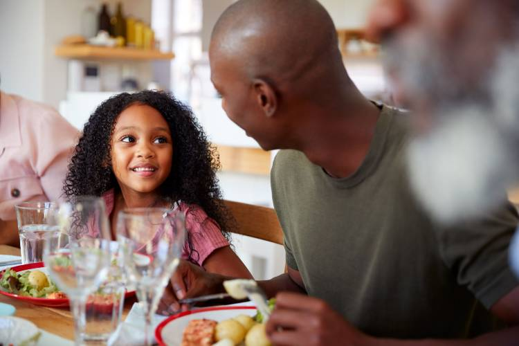 Black family talking and having dinner together, having fun
