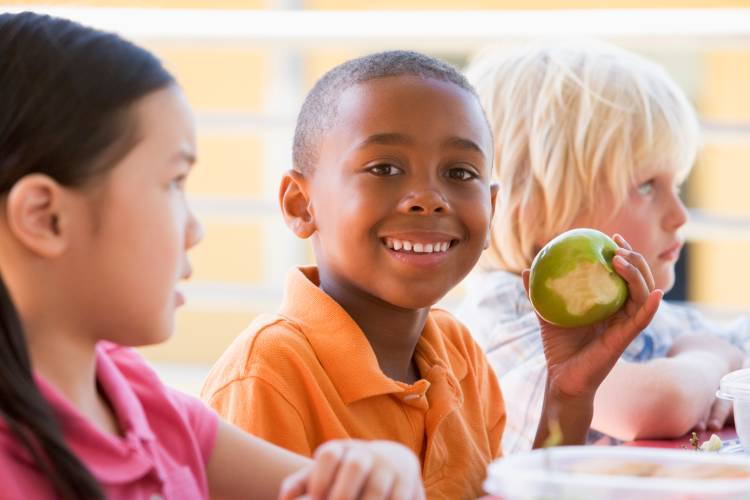 image of young Black student eating an apple at a lunch table with his friends
