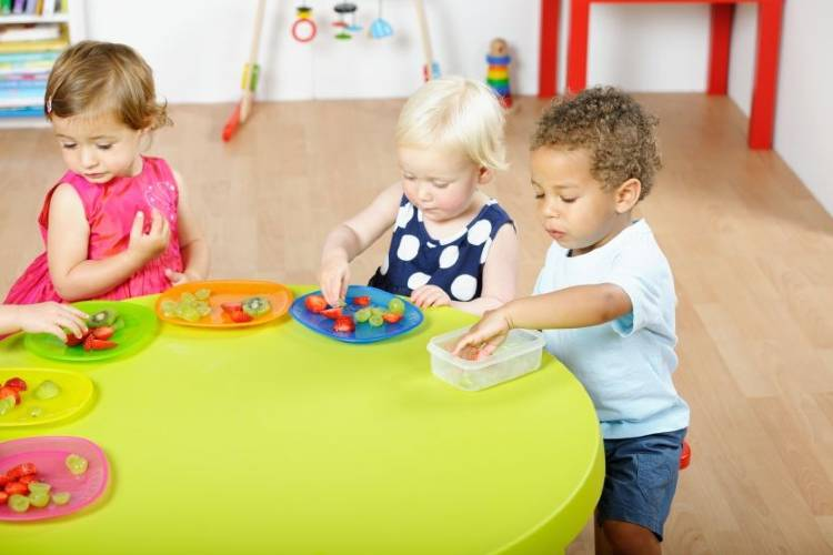 image of 3 children playing with food on a brightly colored table